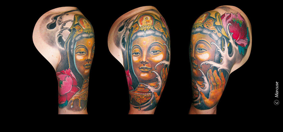 Marcuse | Smilin� Demons Tattoo Studio | tattoo gallery : Buddhist god Kannon in gold with colored peonies and Japanese background on upper arm